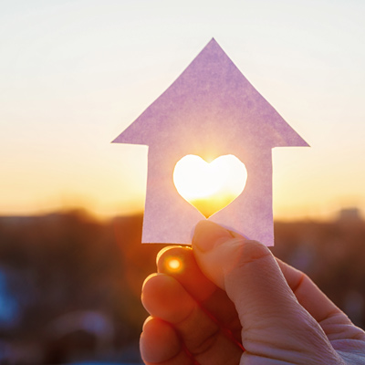 hand holding a paper house with heart cut out of middle against setting sun