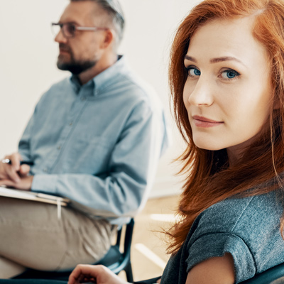 pretty red haired woman in counseling session with male therapist, she is looking at the camera
