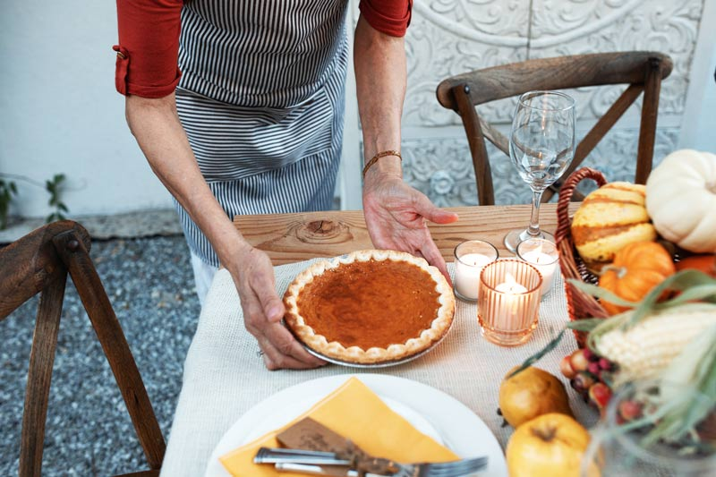 woman setting pumpkin pie on dinner table - sober Thanksgiving