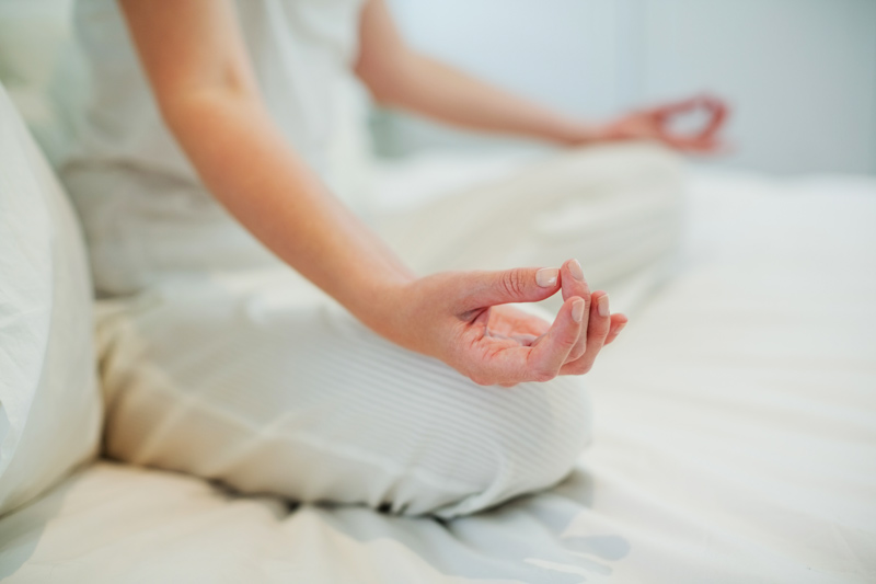 woman meditating on her bed - mindfulness